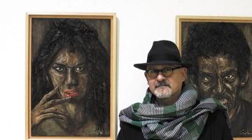 Menpo, pintor tarragoní, amb dues de les seves obres al seu darrera.